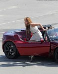 Miley Cyrus rides in the passenger seat of a red Tesla roadster electric car as part of a photoshoot in LA